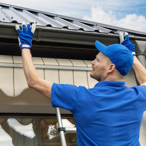 A Roofer Installs a Gutter.