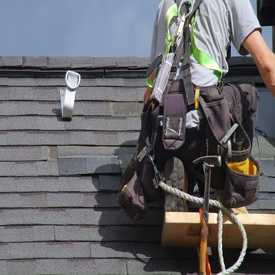 A Roofer Works on Shingles.