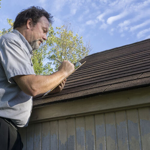 A Roof Insurance Adjuster Examines a Roof.