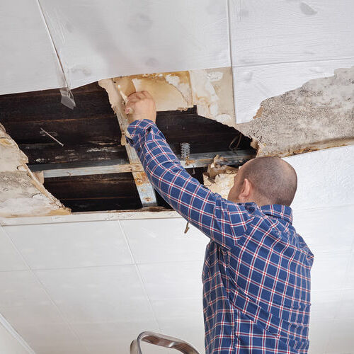 A Technician Repairs a Water Damaged Ceiling.