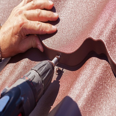 A Roofer Repairs a Roof Tile.