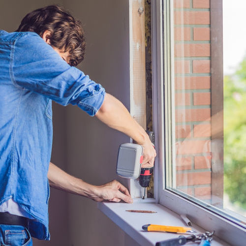 A Technician Installs a Window.